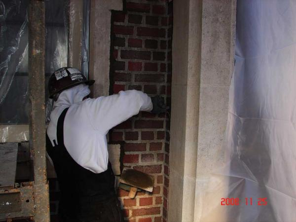 Brick Mason Repairing a Brick Wall