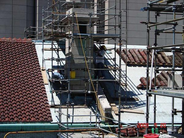Brick Masons Repairing a Building