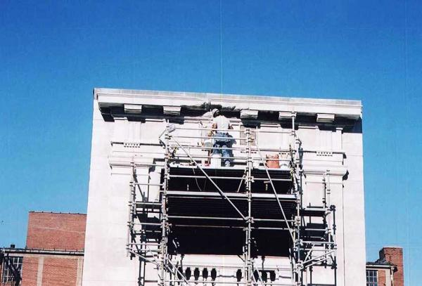 Crew Member Repairing Stone Building
